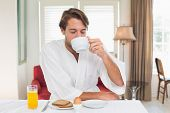 Handsome man having breakfast in his bathrobe drinking coffee at home in the kitchen