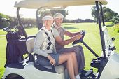 stock photo of buggy  - Happy golfing couple sitting in buggy smiling at camera on a sunny day at the golf course - JPG