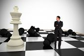 Businessman standing and looking with chessboard against white background with vignette