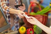 Hand of customer giving credit card to supermarket cashier at checkout