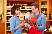 Salesman in supermarket offering bottle of red wine to smiling woman