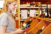 Saleswoman counting wine bottles with mobile data registration terminal