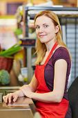 Young smiling cashier sitting at supermarket checkout