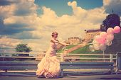 happy bride in elegant wedding-dress hold balloons  outdoor summer day, full body shot, retro colors