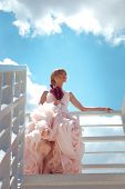 young beautiful bride in elegant wedding dress hold flowers standing on white stairs against sky wit