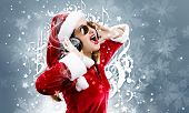 Young attractive Santa girl listening music in headphones