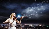 Young woman in white dress playing violin at night