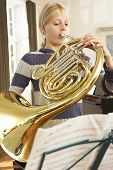 Girl playing French horn at home
