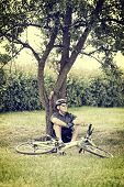 Biker resting under a tree with his bicycle near him