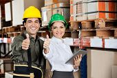 Female supervisor with digital tablet and foreman gesturing thumbs up at warehouse