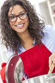 A beautiful girl or young woman looking happy wearing red apron, glasses & cooking in her kitchen at