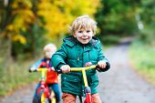 Two Active Brother Boys Running On Bikes In Autumn Forest