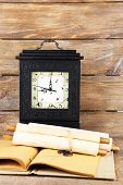Old retro clock and books on wooden background