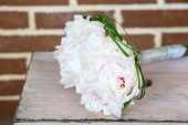 Beautiful wedding bouquet on   wooden ladder on bricks background