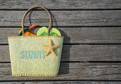 Summer beach bag with text sunny on wood background. Concept of leisure and travel