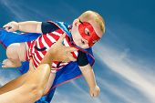 stock photo of guardian  - Happy baby boy wearing superhero costume flying in the sky - JPG