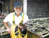 stock photo of elastrator  - Man holding lobster and facing the camera - JPG