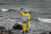 specialist in protective suit checking sample of water  on rocky shore
