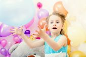 Funny little girl plays with balloon in studio