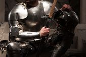 pic of reign  - Closeup portrait of medieval knight in armor with helmet and sword sitting on steps of ancient temple - JPG