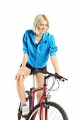Young blond female posing on a bicycle isolated on white background