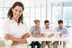 stock photo of half-dressed  - Casual businesswoman smiling at camera with team behind her in the office - JPG