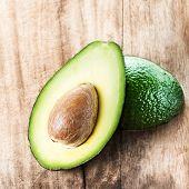 ..avocado Fruit Over Wooden Background. Fresh Green Avocado Fruit Macro.