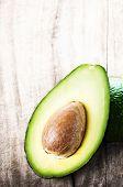 Avocado Fruit Over Wooden Background. Fresh Green Avocado Fruit Macro.