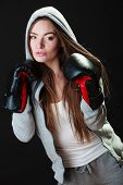 stock photo of martial arts girl  - Martial arts or self defence concept. Sport boxer woman in gloves. Fitness girl training kick boxing on black background