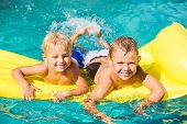 Young Kids Having Fun in Swimming Pool on Yellow Raft. Summer Vacation Fun.
