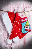 Christmas Stocking And Santa Hat On A Background Of Falling Snow