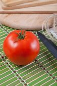 Red tomato on a table with a rope and a knife