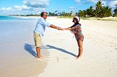 Loving couple relaxing on sandy beach. Caribbean vacation.