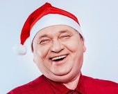 stock photo of laugh out loud  - Close up portrait of laughing out loud middle aged man with red Santa Claus hat and shirt over white background - JPG