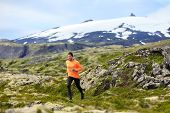 Running man athlete exercising trail runner. Fit male sport fitness model training and jogging outdoors in beautiful mountain nature landscape by Snaefellsjokull, Snaefellsnes, Iceland.