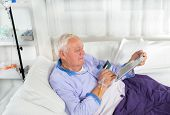 Man in his sickbed uses a credit card payment over the internet