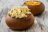 picture of popcorn  - Popcorn and ripe corn in wooden bowls on wooden white background - JPG