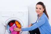 foto of dirty-laundry  - Young housewife is doing laundry with washing machine at home - JPG