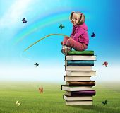 Small girl sits on the pile of books