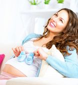 Pregnant Happy Woman holding blue Baby Shoes in her Hands. Mom Expecting Baby boy. Pregnant Woman Belly. Pregnancy. Baby Shower