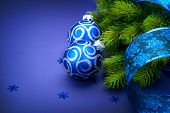 Christmas blue baubles with ribbon and snowflakes over Blue background. Xmas tree New Year decoration art design