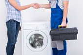 pic of washing-machine  - Handshake of housewife and repairman near the washing machine - JPG