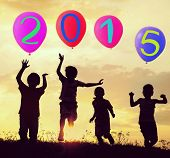 stock photo of meadows  - Silhouette of kids with balloons running and jumping on the summer sunset meadow for happy new 2015 year - JPG
