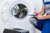 image of machine  - Repairman is repairing a washing machine on the white background - JPG