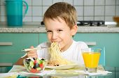 Laughing Boy Eating Spaghetti And Holding The Fork