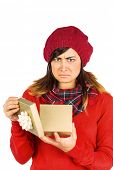 Unhappy brunette opening christmas gift on white background