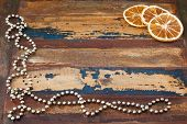 Background Wooden Table With Christmas Chaplet And Pieces Of Dried  Orange