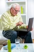 Senior man in living room with laptop