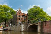 City View Of Amsterdam Canal, Bridge And Typical Houses, Holland, Netherlands.