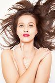 Beautiful brunette girl with long hair, studio shot on white background